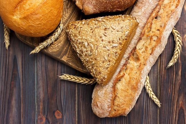 Pão e trigo no fundo de madeira branco. vista superior com espaço de cópia