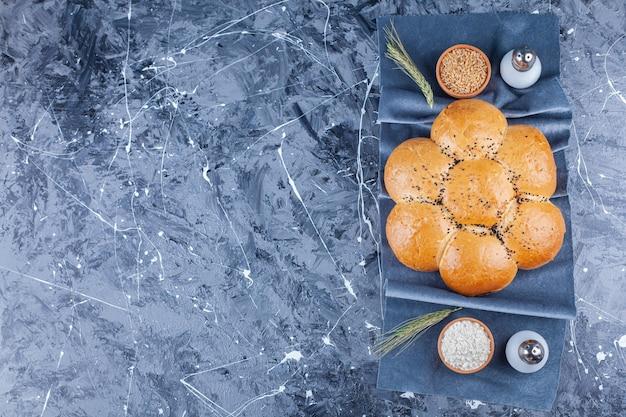Pão em forma de flor redonda, sal, farinha e grãos em pedaços de tecido em azul.