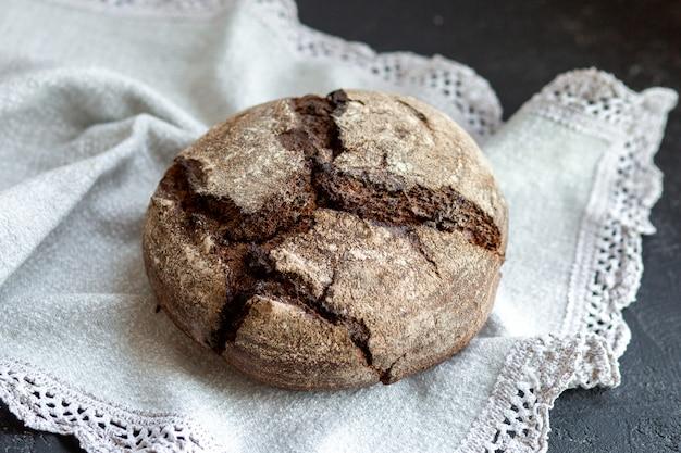 Pão em uma cesta com rolos. padaria fresca. pão preto e branco lindamente dobrado em uma cesta de metal. assar em uma caixa de pão.