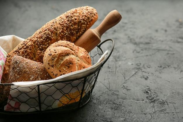 Pão em uma cesta em uma superfície preta. pão sortido em uma cesta de metal. lugar para receita e texto. asse o pão com um rolo e a farinha. pão de centeio, rolos de trigo sarraceno e baguete com sementes.