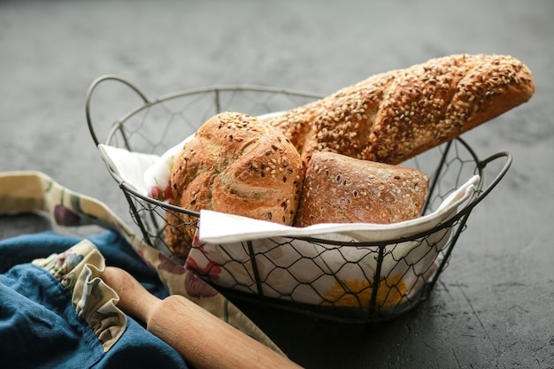 Pão em uma cesta em uma superfície preta. pão sortido em uma cesta de metal. lugar para receita e texto. asse o pão com um rolo e a farinha.