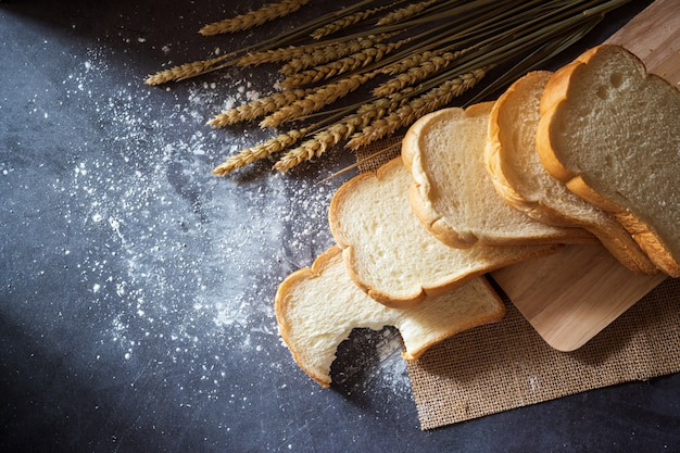 Pão em uma placa de estaca de madeira e as grões do trigo colocadas ao lado com farinha de trigo dispersada.