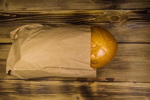 Pão embalado em papel na mesa de madeira