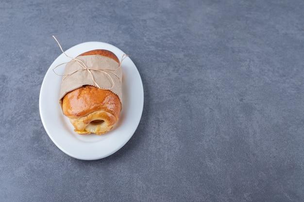 Pão embrulhado em papel no prato, no mármore.