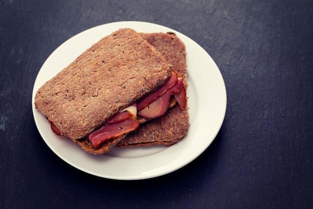 Pão escuro com carne defumada em chapa branca