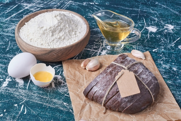 Pão escuro com ingredientes na mesa azul.