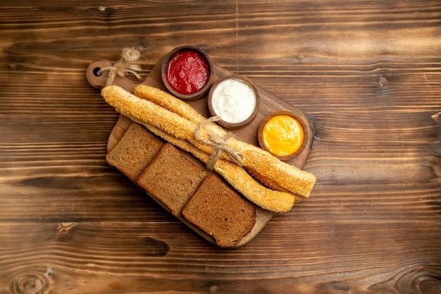 Pão escuro de cima com pãezinhos e temperos na mesa marrom.