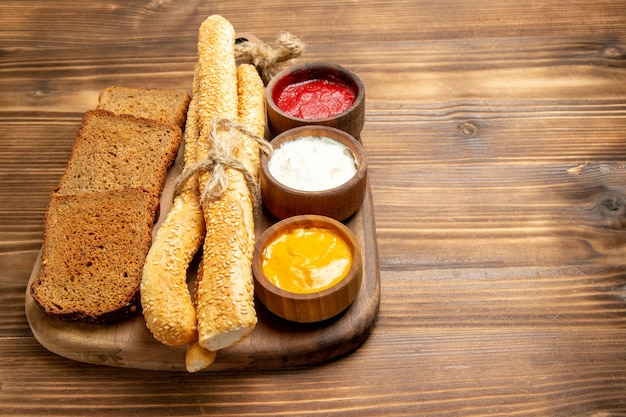 Pão escuro de frente com pãezinhos e temperos na mesa de madeira marrom.