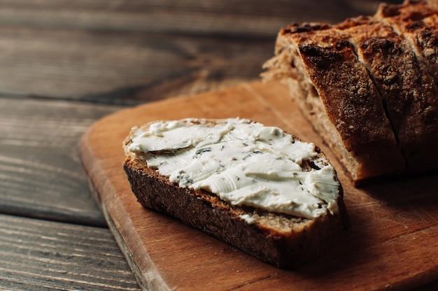 Pão escuro é espalhado com queijo cottage com ervas em um corte sobre uma tábua de madeira sobre uma mesa de madeira em estilo rústico.