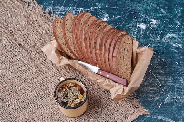 Pão escuro em uma bandeja de madeira com bebida.