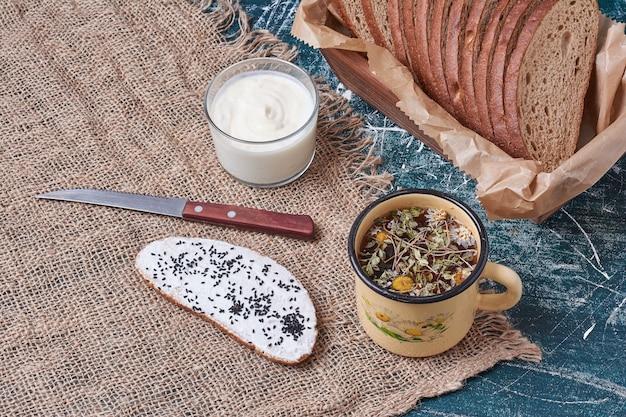 Pão escuro em uma bandeja de madeira com uma fatia de torrada e bebida.