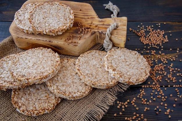 Pão estaladiço arejado, redondo e crocante de trigo sarraceno em fundo de madeira