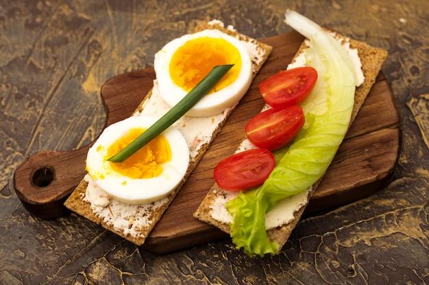 Pão estaladiço com ovo, tomate cereja e uma folha de alface fresca em uma tábua de madeira. lanches. comida dietética