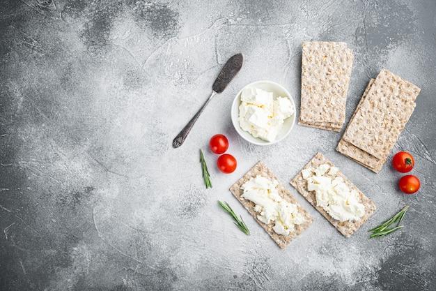 Pão estaladiço com queijo feta, mesa de pedra cinzenta, vista de cima plano