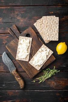 Pão estaladiço com queijo feta, na velha mesa de madeira escura, vista de cima plana