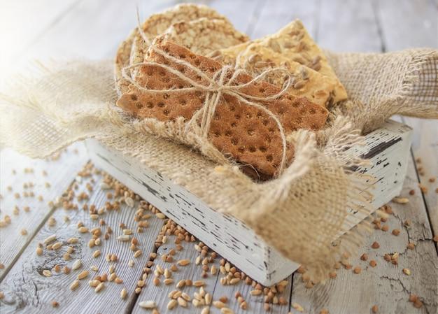 Pão estaladiço redondo de trigo sarraceno, pão estaladiço de trigo e pão estaladiço com sunflowe em caixa de madeira vintage