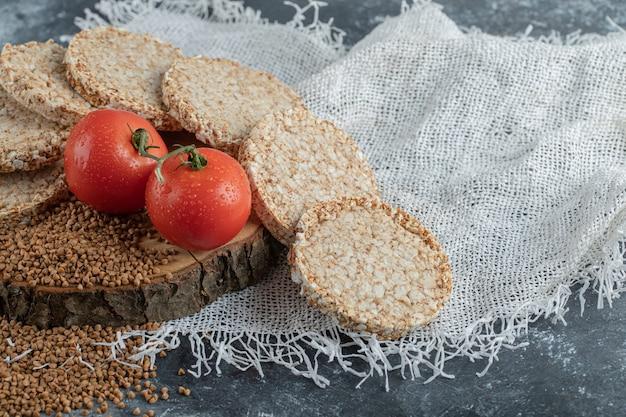 Pão estaladiço, tomate e trigo sarraceno cru na peça de madeira