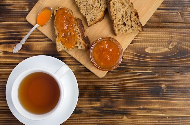 Pão fatiado com geléia de damasco na tábua e chá na xícara branca sobre o fundo de madeira marrom. vista superior. copie o espaço.