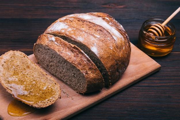 Pão fatiado com mel numa mesa castanha