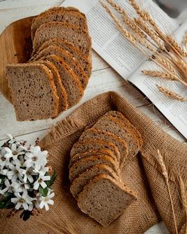 Pão fatiado com ramo de trigo e flores