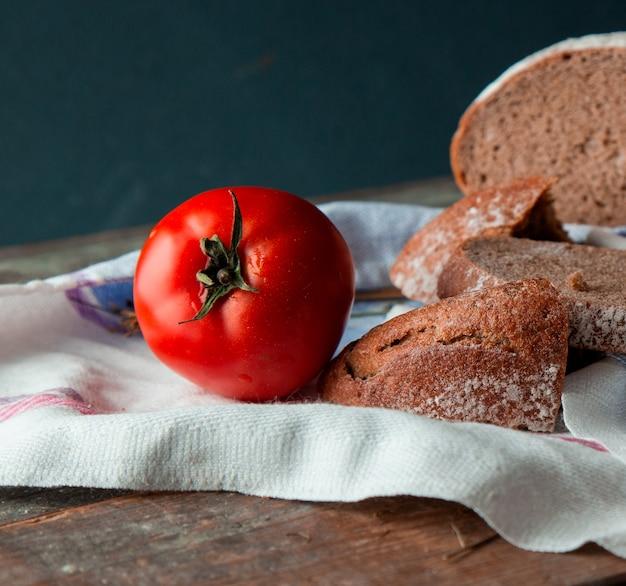 Pão fatiado com um tomate inteiro em uma toalha de cozinha branca.