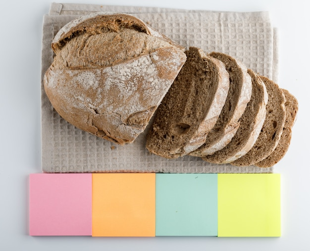 Pão fatiado com vista lateral para notas adesivas coloridas sobre uma superfície branca