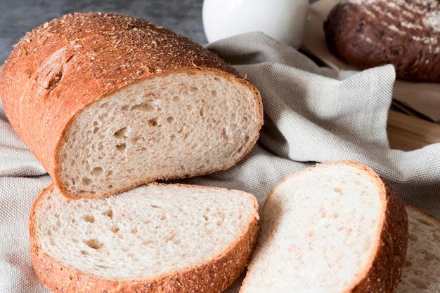 Pão fatiado de ângulo alto com toalha de cozinha