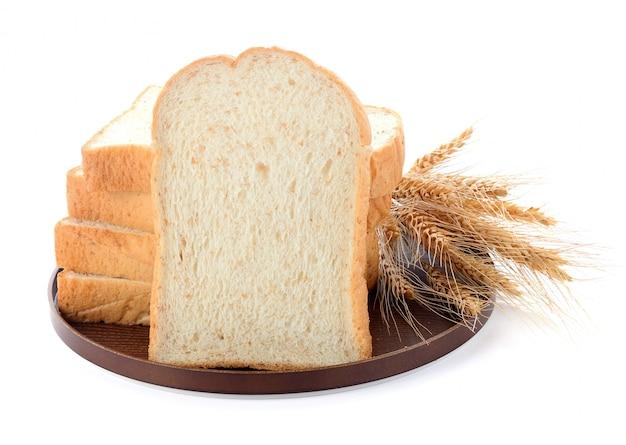 Pão fatiado e trigo na placa de madeira isolada no branco