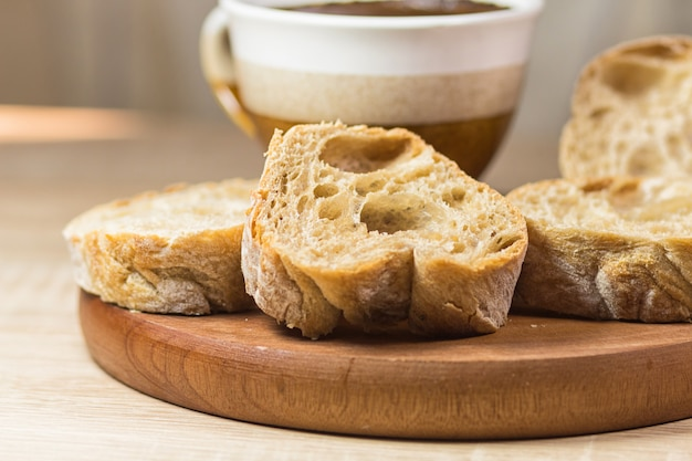 Pão fatiado e uma xícara de café em uma placa de madeira