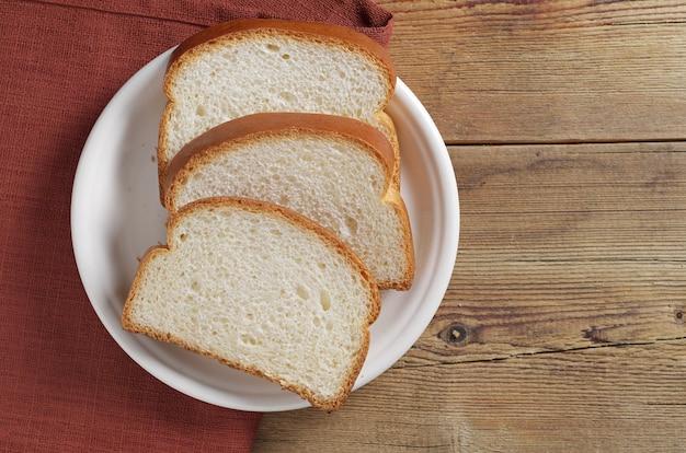 Pão fatiado em um prato na mesa de madeira, vista superior