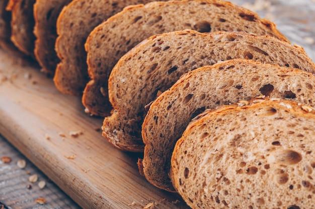 Pão fatiado em uma placa de corte em uma mesa de madeira e vista lateral de superfície cinza.