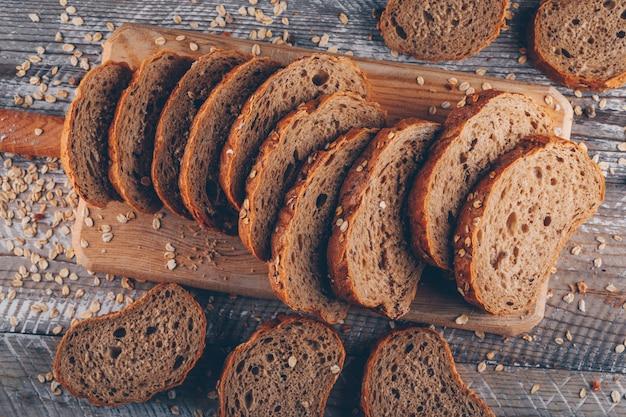 Pão fatiado em uma tábua na superfície de madeira, vista superior