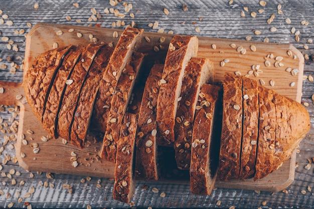 Pão fatiado em uma tábua sobre uma superfície de madeira
