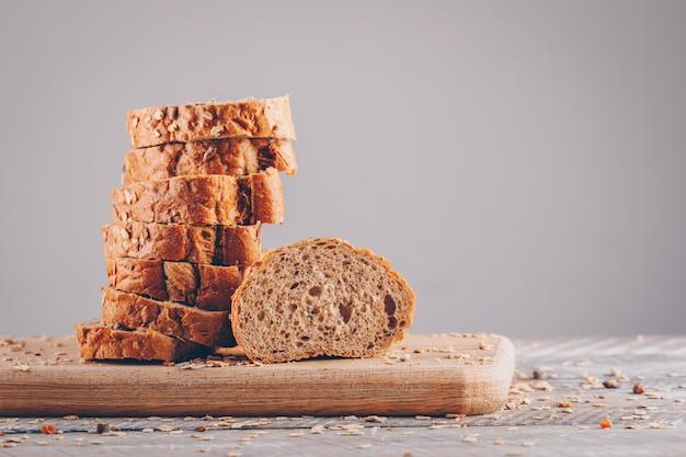 Pão fatiado em uma vista lateral de tábua sobre uma mesa de madeira e superfície cinza
