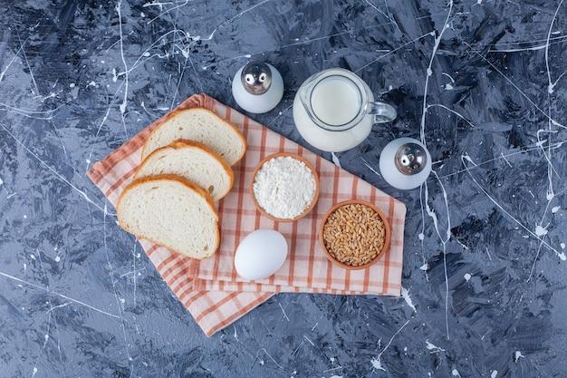 Pão fatiado, grãos, ovo e leite em um pano de prato, na superfície azul. .