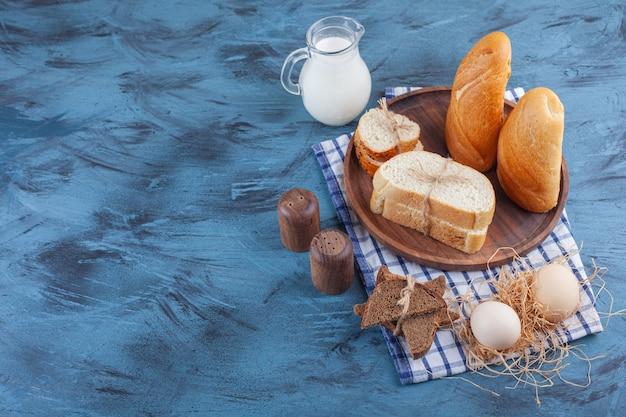 Pão fatiado, jarro de leite e ovo em um pano de prato, na mesa azul.