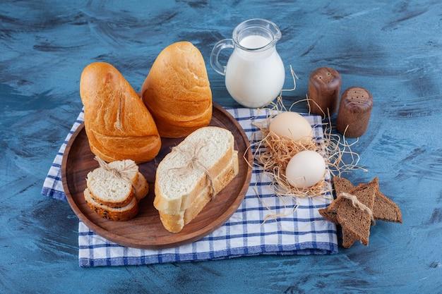 Pão fatiado, jarro de leite e ovo em um pano de prato, na superfície azul.