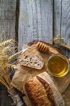 Pão fatiado, mel, trigo, fundo de madeira rústico