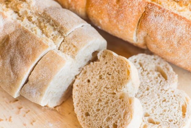Pão fatiado na mesa de madeira de perto