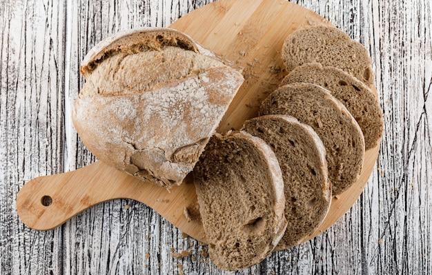 Pão fatiado no na tábua sobre uma superfície de madeira. vista do topo.