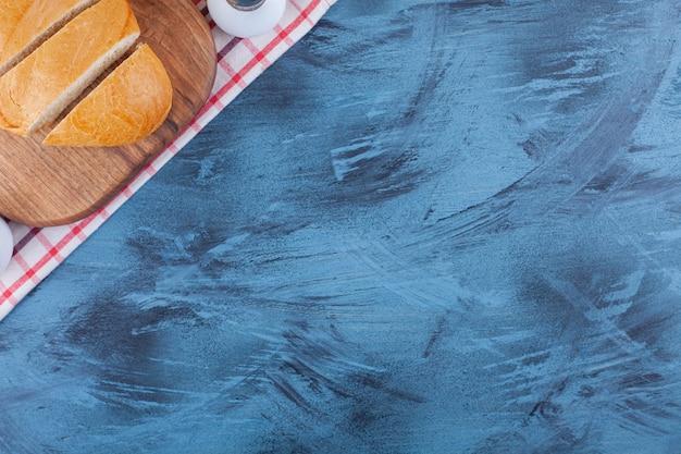 Pão fatiado numa tábua em toalha de chá em azul.