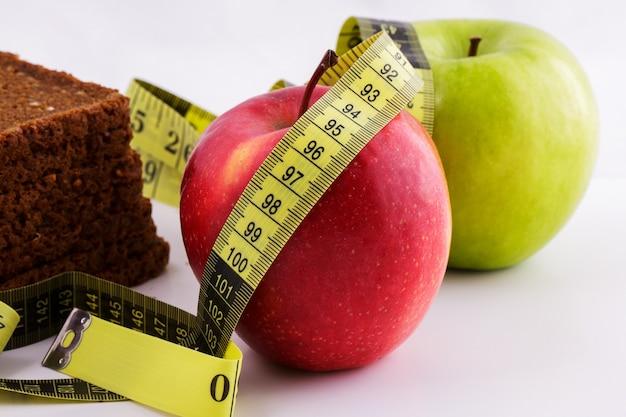 Pão fatiado preto e maçãs verdes e vermelhas repousam em uma parede branca com uma fita métrica amarela, conceito de dieta