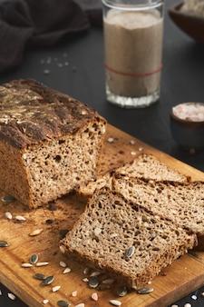 Pão fermentado, pão integral de centeio com sementes de abóbora e girassol. fermento de fermento na mesa. produto biológico orgânico autêntico com massa fermentada caseira. produto artesanal, fatias de pão a bordo
