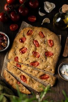 Pão focaccia caseiro italiano tradicional com tomate e alecrim em fundo de madeira rústico