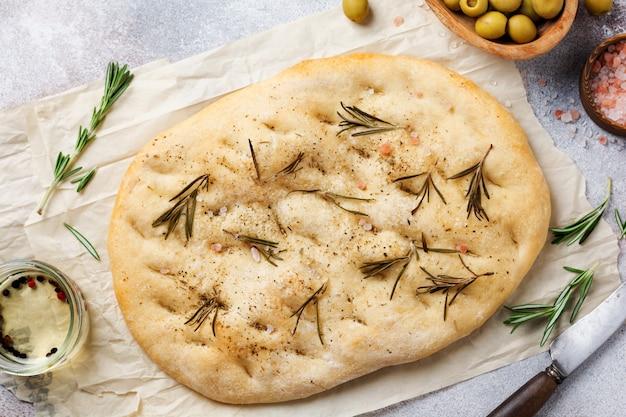 Pão focaccia caseiro tradicional italiano recém-assado no forno com temperos e alecrim em papel vegetal e fundo cinza claro. vista do topo.
