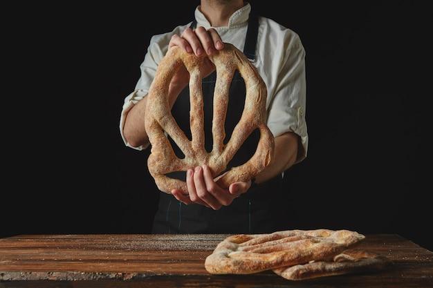 Pão fougas delicioso recém-assado nas mãos de um homem em um fundo preto
