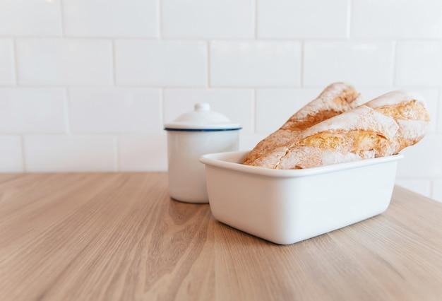 Pão francês e uma jarra na mesa e parede de tijolo cerâmico branco