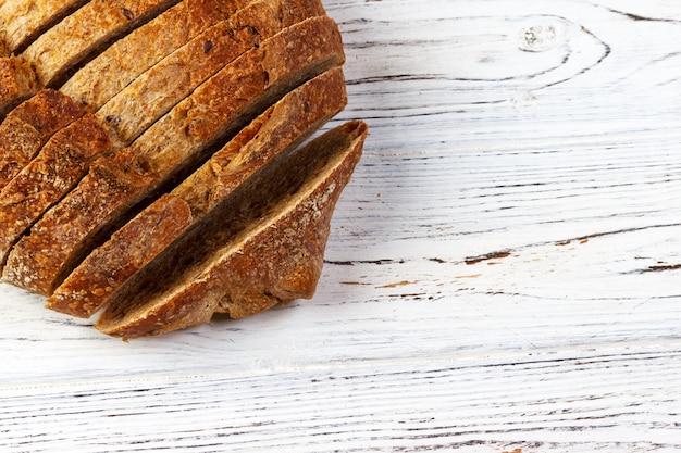 Pão francês fatiado, em uma placa de madeira com espaço para texto