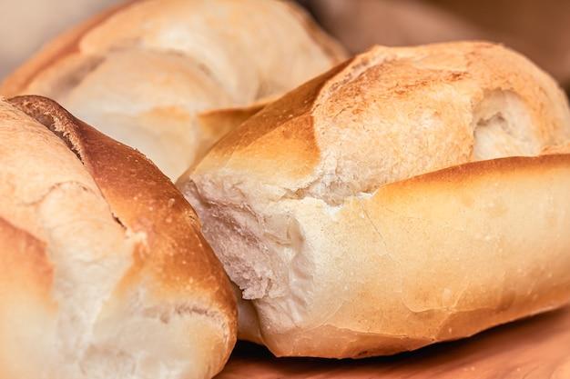 Pão francês na placa de madeira em foto macro