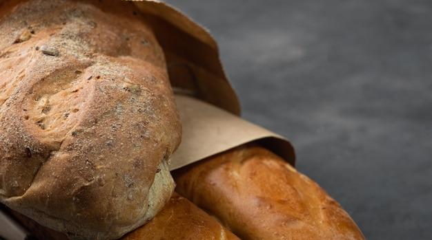 Pão fresco apetitoso e baguete com uma crosta crocante sobre um fundo escuro em um saco de papel. espaço livre à direita, baguete e pão à esquerda.